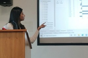 Aayushi at the podium, talking a hybrid class through a slide projected in a classroom.