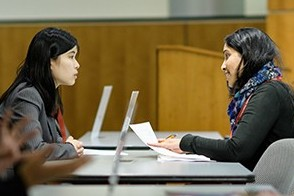 A female student speaks to a recruiter at a Stevens career event.