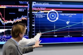 Professor gesturing to a large screen of data in Stevens' Hanlon Financial Systems Lab