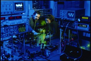 A professor and a student in an optics lab looking at a laser.