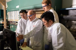 Three students in a lab with a professor
