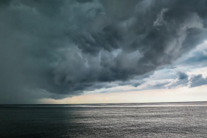 Storm clouds above calm ocean