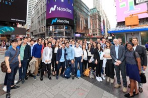 A large group of graduate students and faculty in professional dress stand in Times Square.