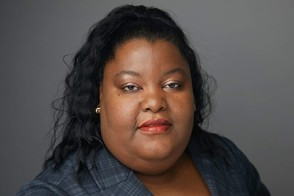 Headshot of Sheryl Duffus, wearing a blazer, against a neutral gray background.