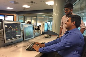 Two male students working with Bloomberg data in the finance lab.