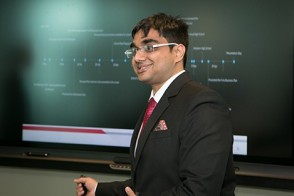 A male student leads a presentation as a project timeline is displayed in the background.