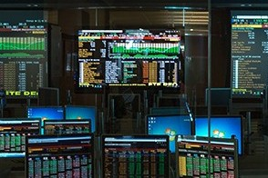 A darkened lab showing multiple Bloomberg terminals.