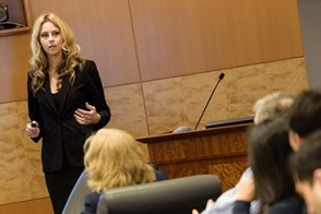 A female Stevens student leads a presentation in a corporate boardroom.