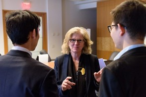 A professor speaking with two male students dressed in suits during a research networking event.