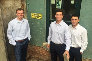 Three students on the Fliptrack team in front of a foreclosed property in Hoboken.