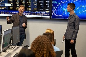 Dr. George Calhoun stands with alumnus Dakota Wixom in the high-tech Hanlon Lab. Behind them is a display of live Bloomberg data.