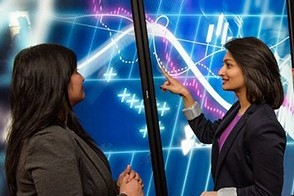 Three female students examine data on a screen outside the Hanlon Lab at Stevens.