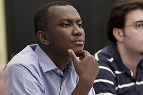 Two male students listen to a lecture in a graduate finance class.