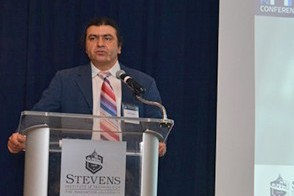 Dr. Ionut Florescu, in a blue jacket and red tie, welcomes a packed house to the annual conference at Stevens.