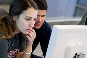 A male and female student look at data on a Bloomberg terminal in the Hanlon Lab.