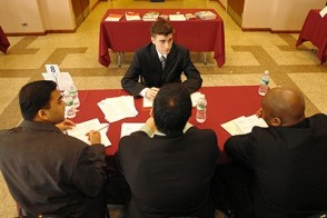 Company representatives interview a Stevens student on campus about an internship.