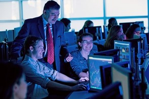 Dr. Khaldoun Khashanah points out some data on a Bloomberg screen to a male and a female student in the Hanlon lab.