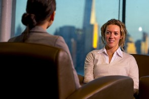 Two women having a conversation in a lounge where the New York skyline is visible in the background.