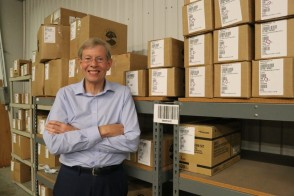 Photo of Walter Ulrich '68 in the warehouse at the non-profit Medical Bridges, Inc., with boxes of medical supplies behind him.