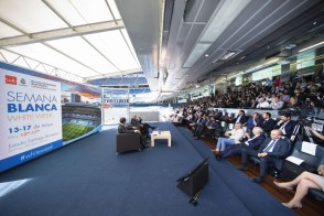 Photo of two speakers in front of a crowd the White Week event at Santiago Bernabéu Stadium in Madrid.