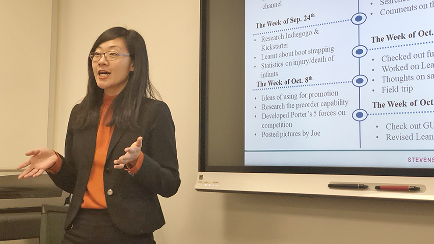 An MBA student leads a presentation on the Stroller Controller in a conference room.