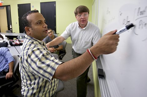 Dr. Kevin Ryan walks a student through a problem in a telecommunications class.