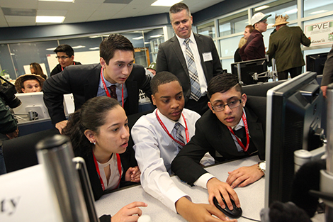 Student frantically execute trades in the Stevens trading lab while alumnus John Schwall, COO of IEX Group, looks on.
