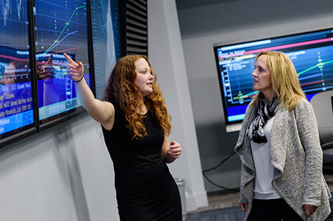 Victoria Piskarev, in a black dress, points to Bloomberg data on a large screen as she presents to Michelle Crilly, in a white sweater.