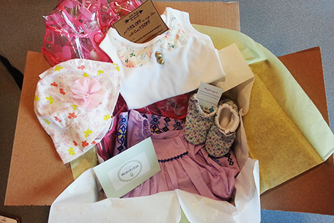 A girl's box from Wee Wardrobe, with hats, booties, shirts and other clothes.