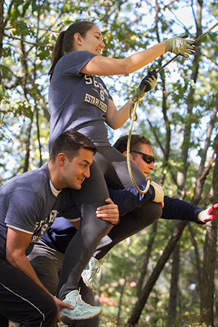 Students work together to complete an obstacle during the leadership retreat at West Point.